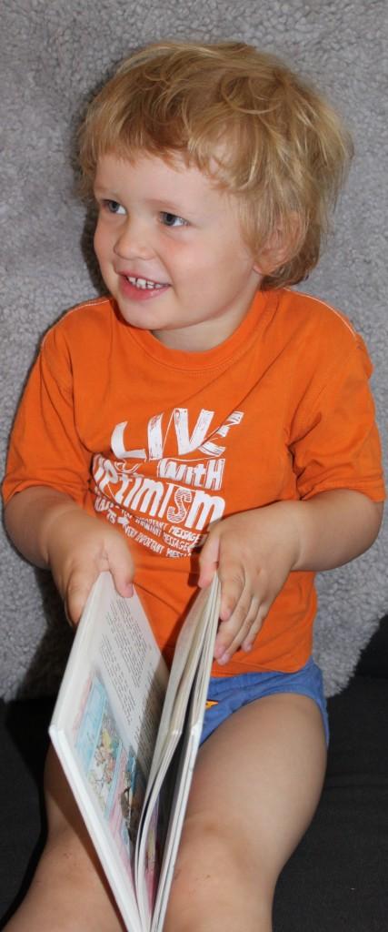 Sindre smiler med bok